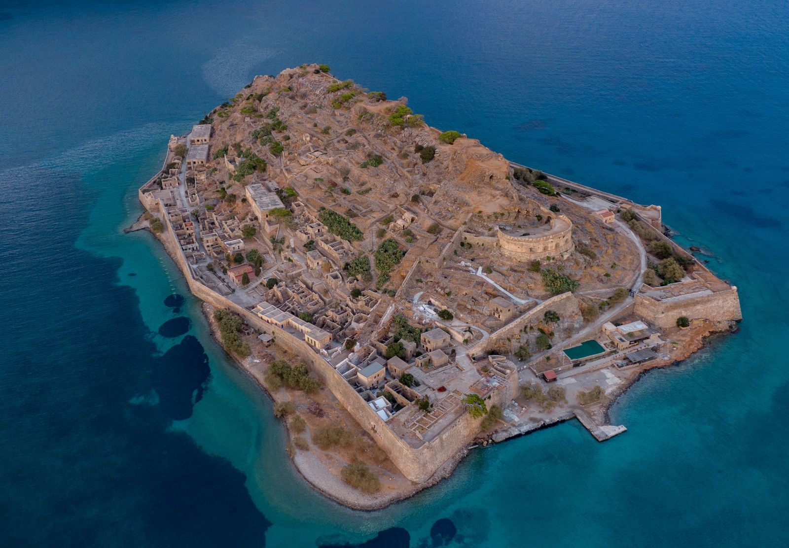 Aerial view of the island of Spinalonga in the blue sea waters off the coast of Crete in Greece, the island is a stone fortress. Aerial photography