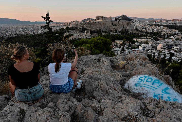 Touristen auf einem Athener Hügel mit Blick auf die Akropolis: Kreuzfahrtschiffe dürfen Piräus wieder anlaufen