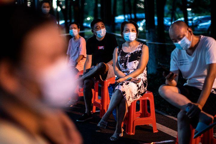 Bewohnerinnen und Bewohner von Wuhan warten auf den Coronatest