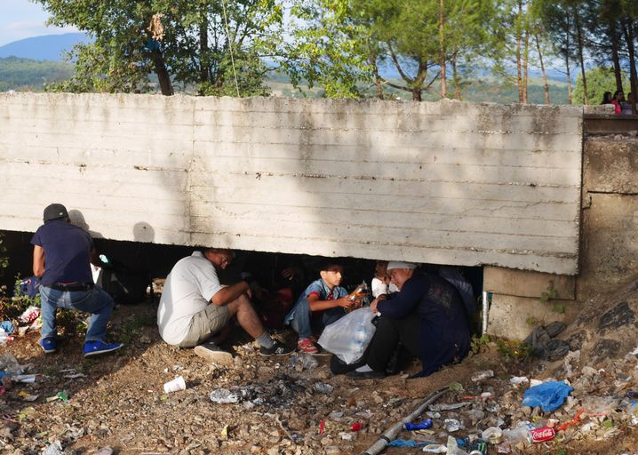 Syrian refugees seek cover under the train tracks during a short rain storm.