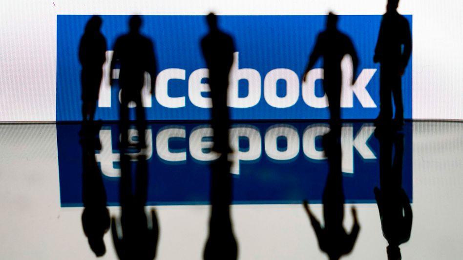 Schattenhafte Gestalten vor einem Facebook-Logo
