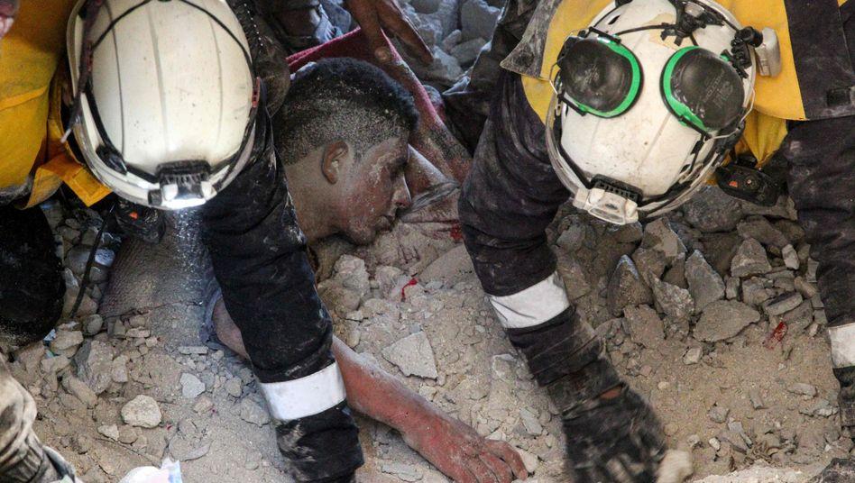 Mitglieder der Weißhelme, einer syrischen Zivilschutzorganisation, bergen einen Überlebenden aus den Trümmern eines bombardierten Hauses in Idlib