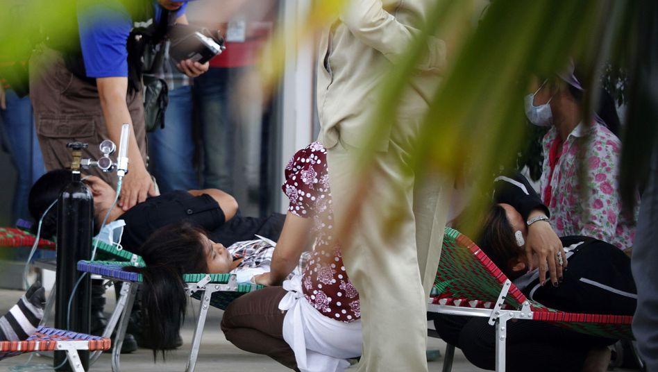 Erste Hilfe: Zusammengebrochene Textil-Arbeiterinnen im Juli in Phnom Penh