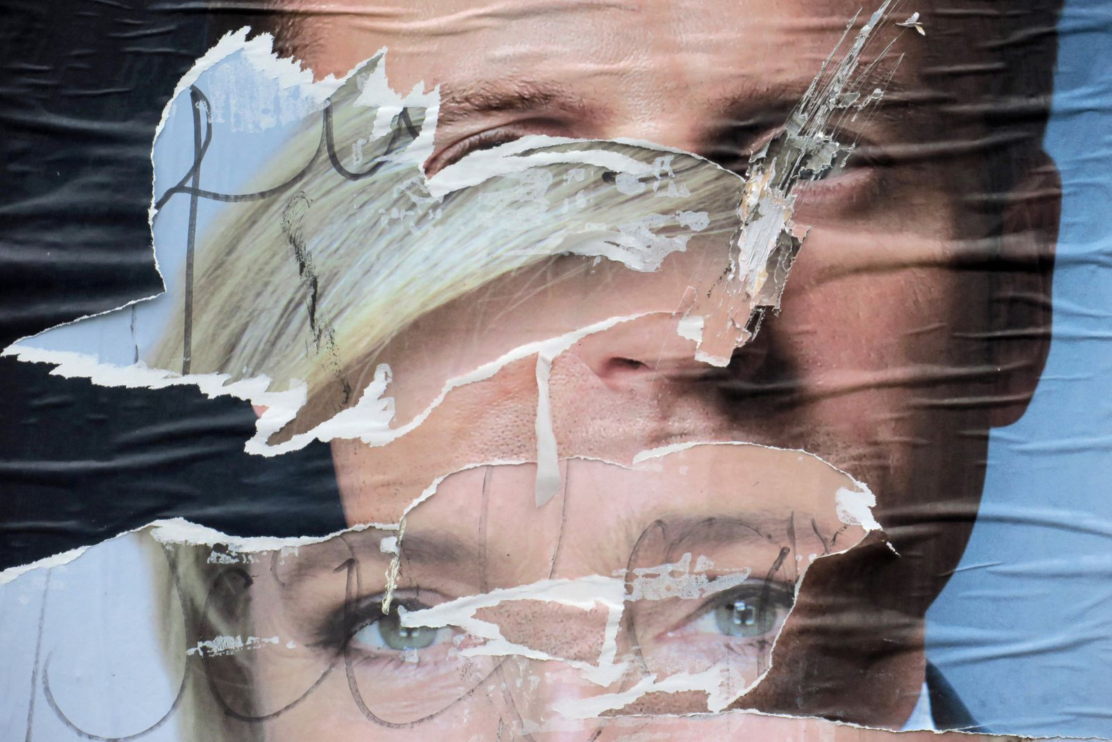 Torn and overlapping official posters of candidates for the 2017 French presidential election Marine Le Pen, of French National Front (FN) political party, and Emmanuel Macron, head of the political movement En Marche !, or Onwards !, in Cambrai