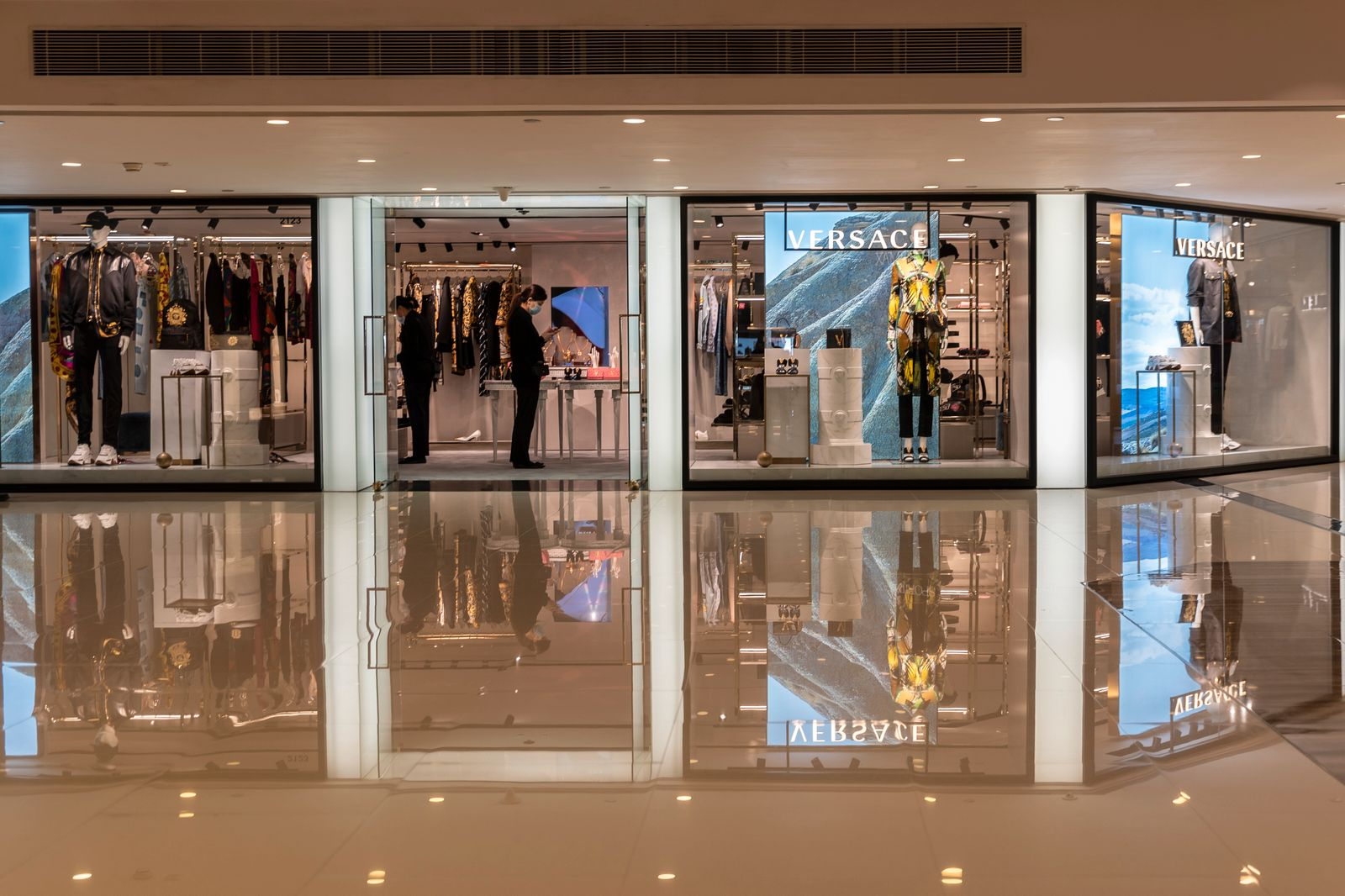 A masked shop keepers of the luxury brand Versace inside the