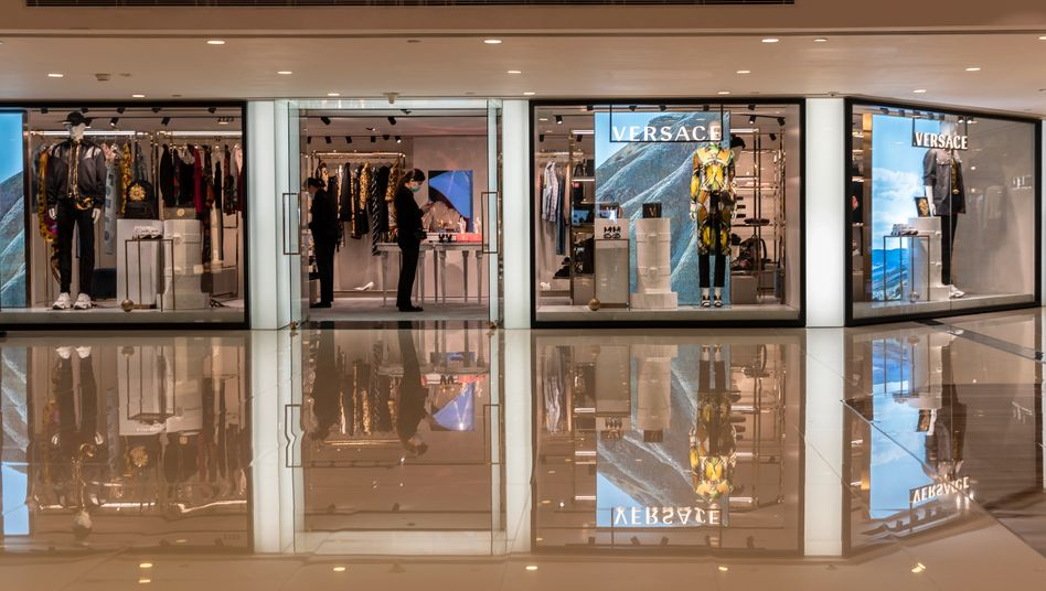 "Ein mit Mundschutz ausgestatteter Verkäufer steht am Eingang der leeren Versace-Boutique in der verwaisten Hongkonger ""Harbour City Shopping Mall"""