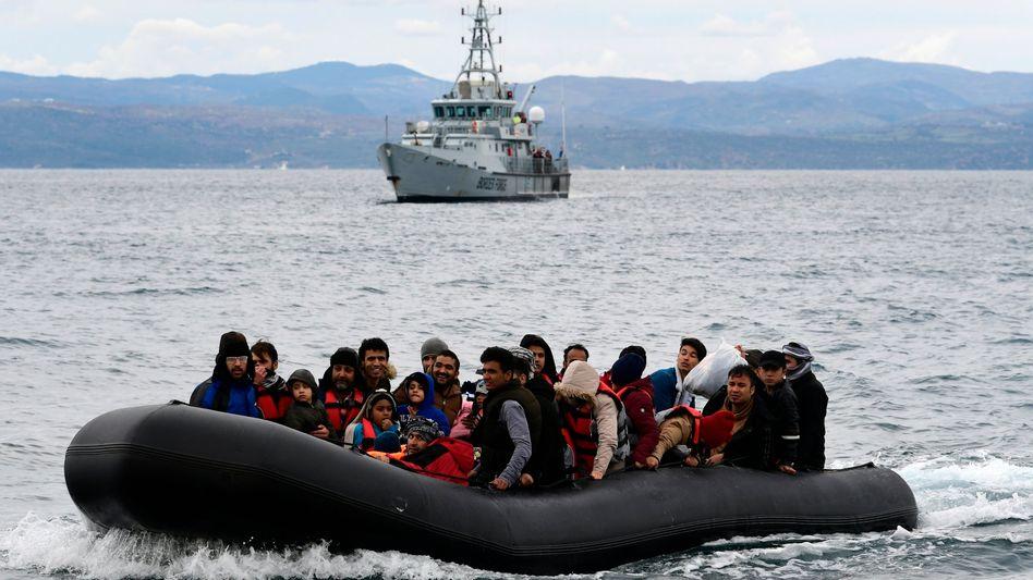 Flüchtlingsboot in der Ägäis, begleitet von einem Frontex-Schiff
