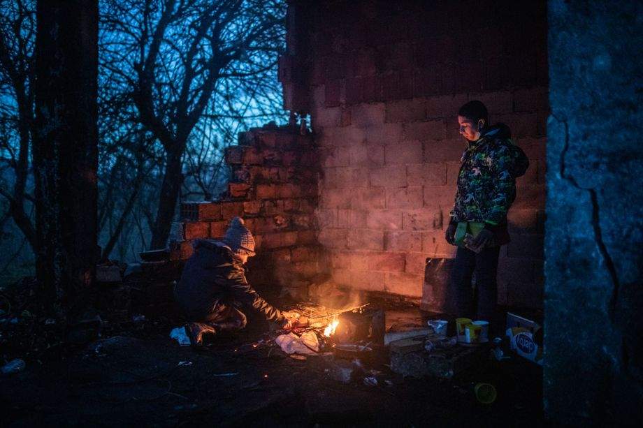 Trying to survive in below-zero winter temperatures: Teenagers light a fire to keep warm.