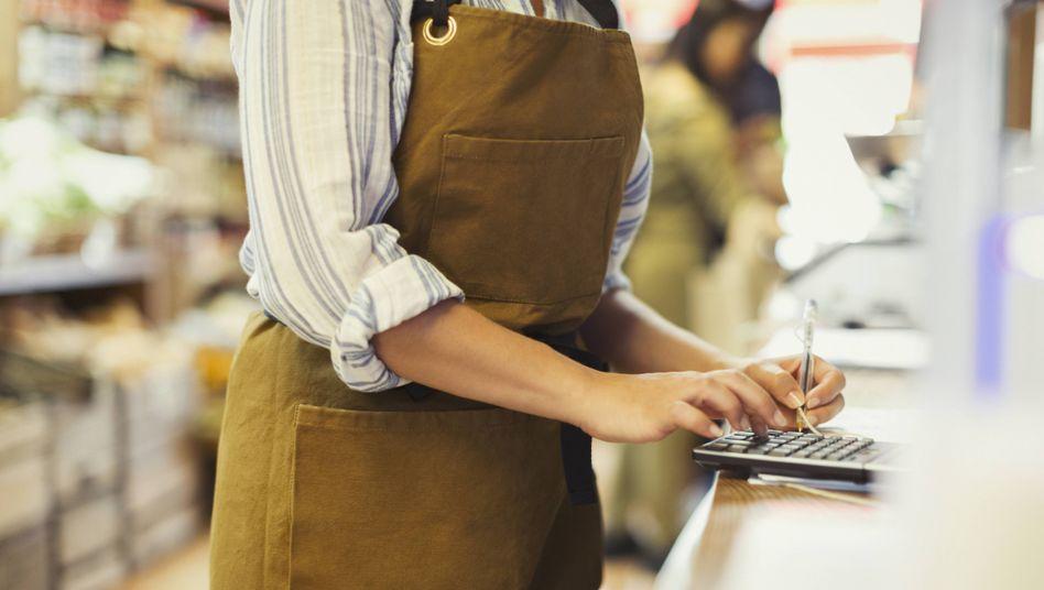 Junge Frau beim Kassieren (Symbolbild)
