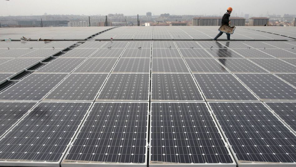 A worker walks past sets of solar panels on the rooftop of a Nanjing South Railway Station, currently under construction in China.