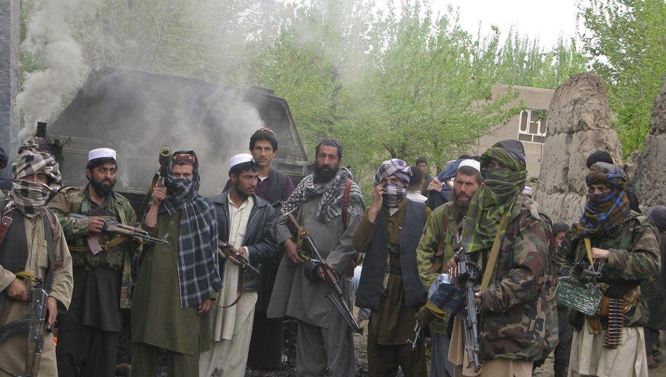 Taliban vor einem ausgebrannten Bundeswehrfahrzeug nahe Kunduz: Die Aufständischen dehnen ihre Macht immer weiter aus