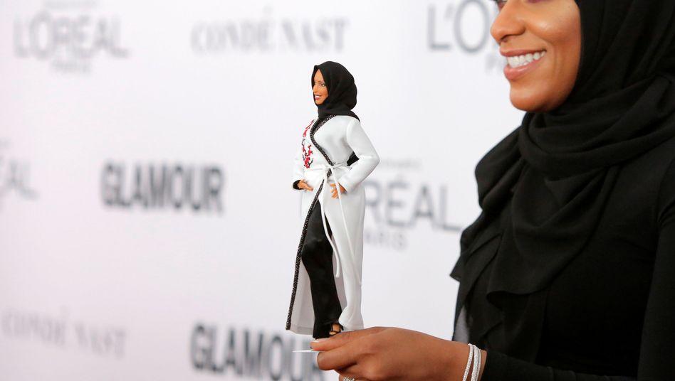 Säbelfechterin Ibtihaj Muhammad hält ihre Doppelgängerin in der Hand - als Barbie