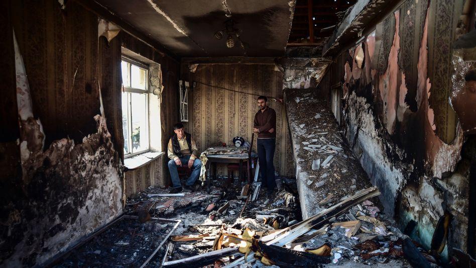 Bewohner der Stadt Tartar in Aserbaidschan betrachten die Schäden an einem Haus nach einem Beschuss durch armenische Streitkräfte