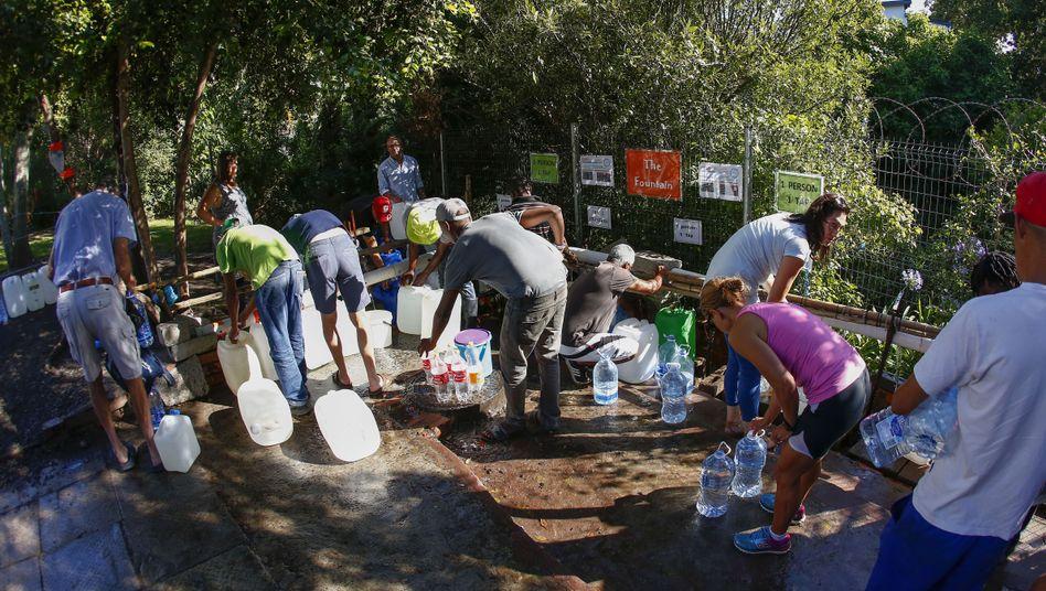 Menschen in Kapstadt stehen für Wasser an