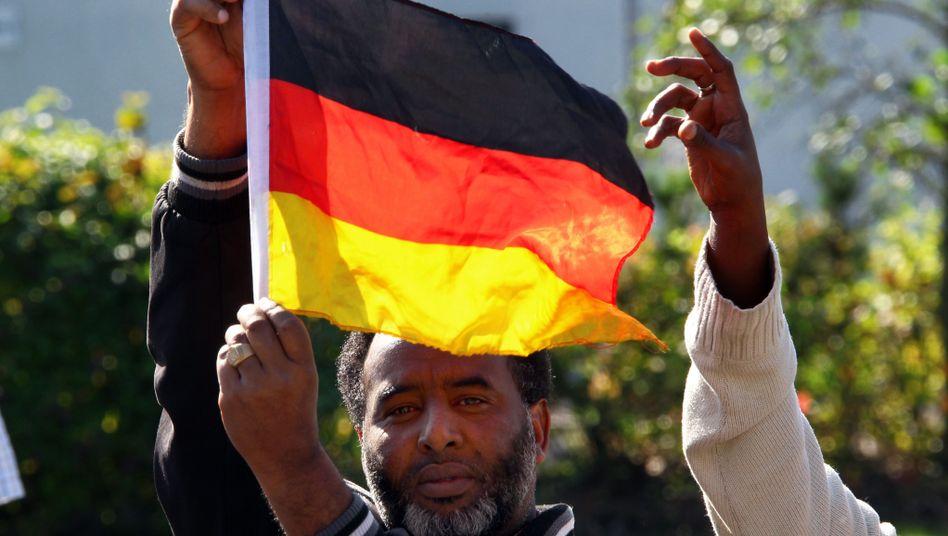 Flüchtling mit Deutschlandflagge: Wie läuft es mit der Integration?