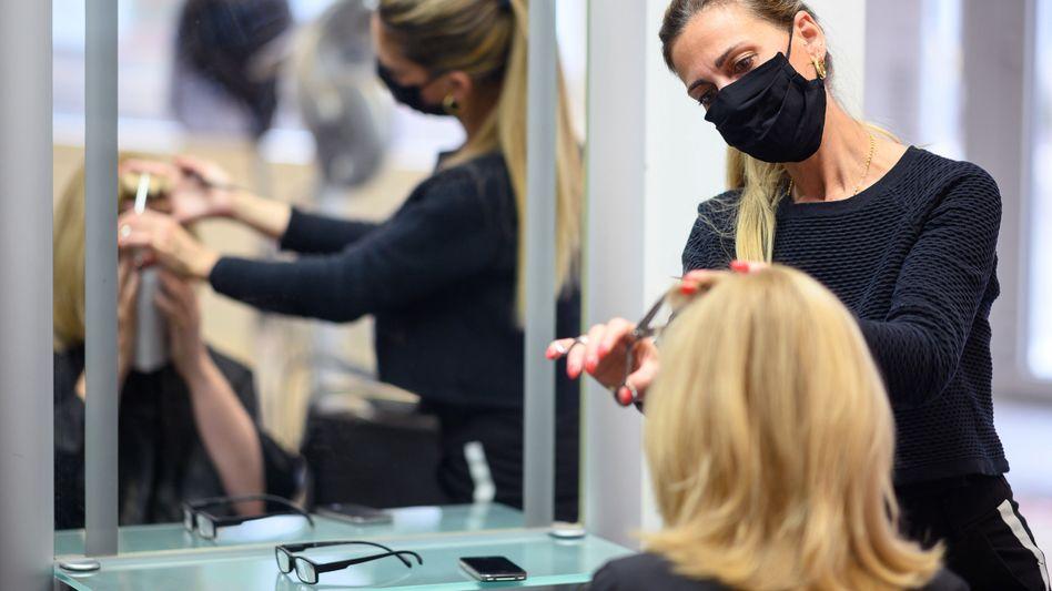Immer mit Maske: Friseurin schneidet in einem Salon den Pony einer Kundin