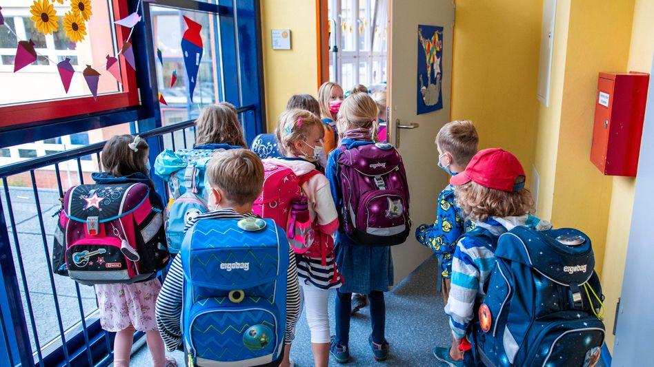 Eine erste Klasse in Rostock geht in ihren Klassenraum: Größte Ansammlungen Ungeimpfter in geschlossenen Räumen