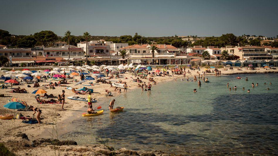 Urlauber an einem Strand im Süden von Menorca: Seit Ende Juni sind die Coronazahlen in Spanien stark gestiegen