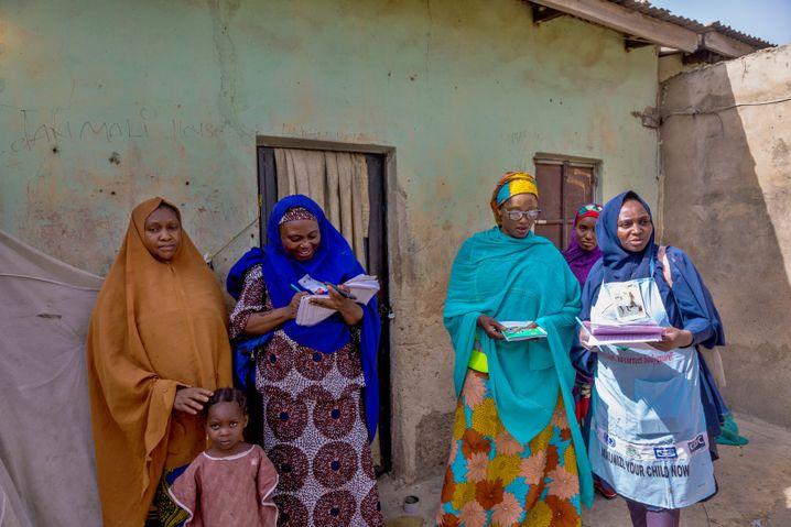 Ramatu Abdullahi überprüft, ob das Kind neben ihr bereits geimpft worden ist und trägt das Ergebnis in ihre Liste ein