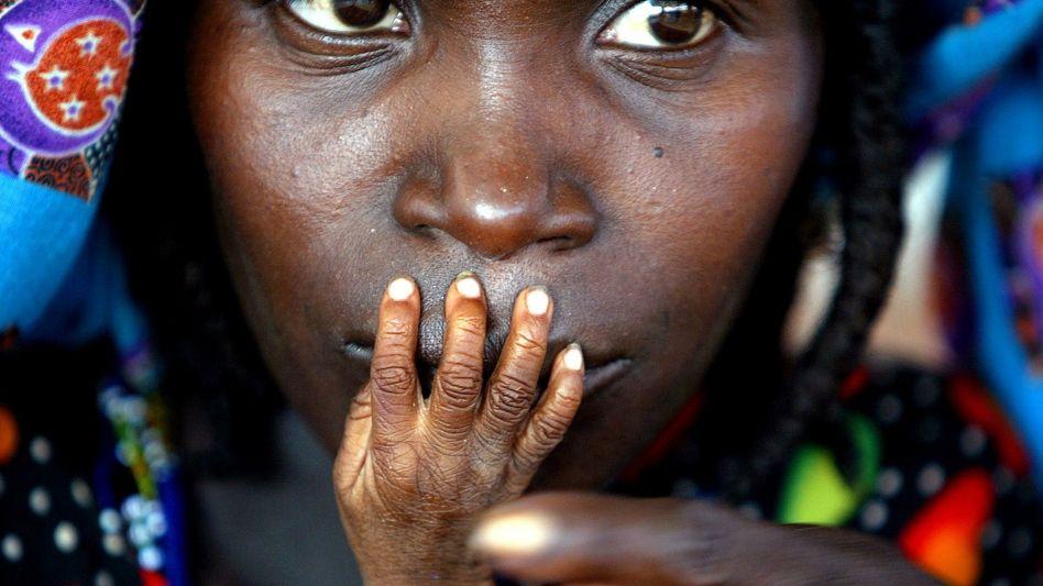 Frau in Niger mit der Hand ihres unterernährten Kindes vor dem Mund (Archiv)