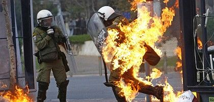 A riot policeman in flames runs to escape during a riot in Athens on Dec. 12: Dashed hopes and opportunities