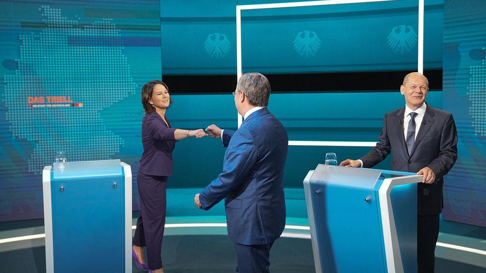 Annalena Baerbock (Grüne) und Armin Laschet (CDU) begrüßen sich neben Olaf Scholz (SPD) im Studio zum ersten Triell
