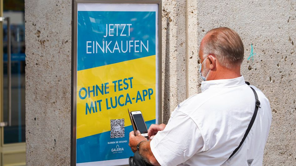 Ein Mann in Berlin nutzt die Luca-App, um am Alexanderplatz einkaufen zu können