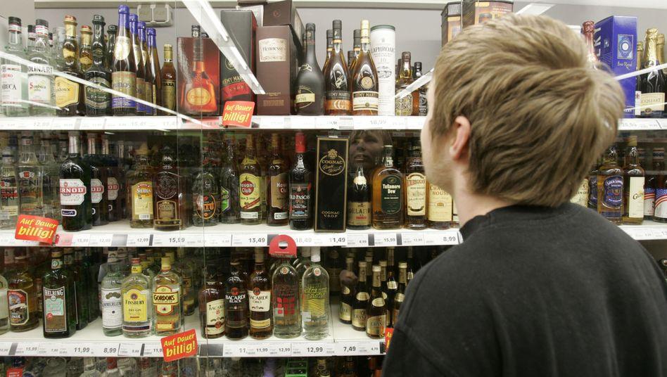 Junger Mann vor Spirituosenregal (Archivbild): Baden-Württemberg hat ein nächtliches Verkaufsverbot für Alkohol verhängt