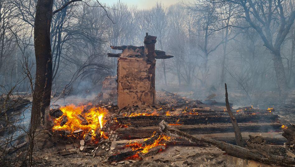 Ein unbewohntes Haus ist bei einem Waldbrand in der radioaktiv belasteten Sperrzone um das Kernkraftwerk Tschernobyl niedergebrannt