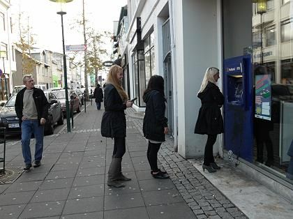 Customers queue to get cash from an ATM.