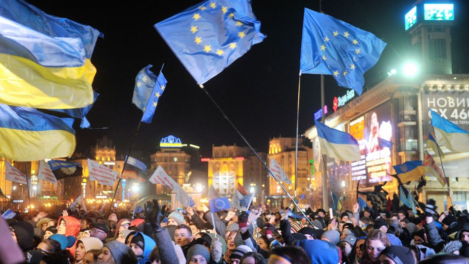 Ukrainians wave flags of Ukraine and of the European Union in central Kiev on Wednesday.