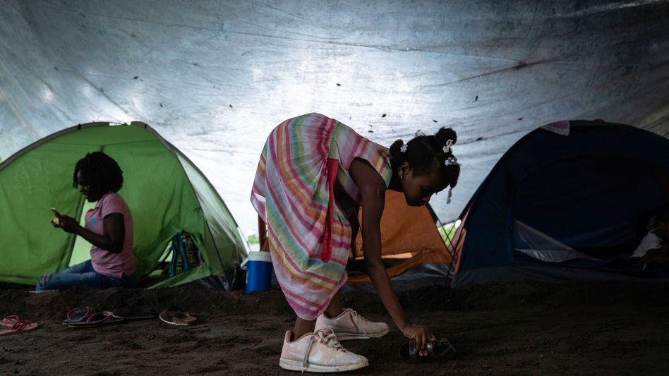 Ein geflüchtetes Mädchen spielt vor einem Zelt in Tapachula, Mexiko