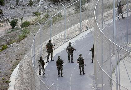 "Spanish soldiers patrol the border which separates Spain""s North African enclave of Ceuta from Morocco in Ceuta."