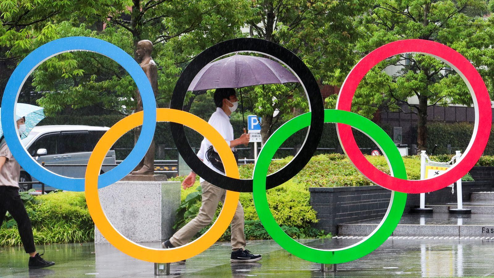 People walk outside the Japanese Olympic Committee (JOC) headquarters near the National Stadium