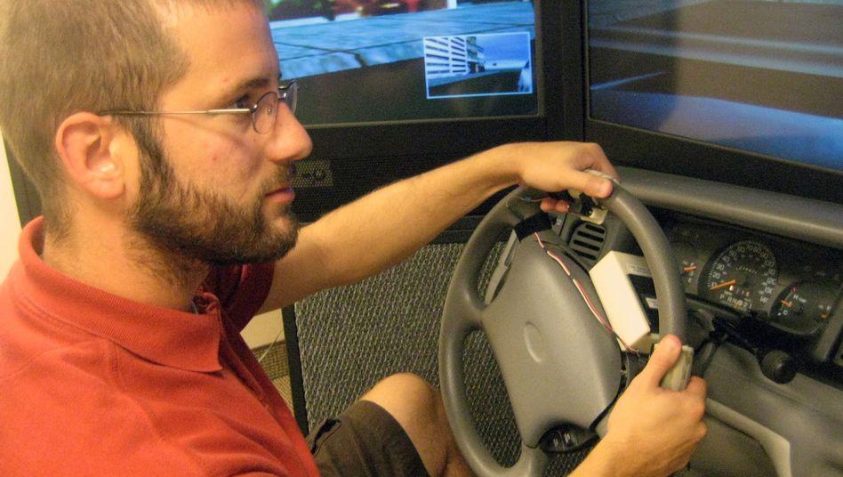 Testperson am Fahrsimulator: Richtungshinweise an die Daumen