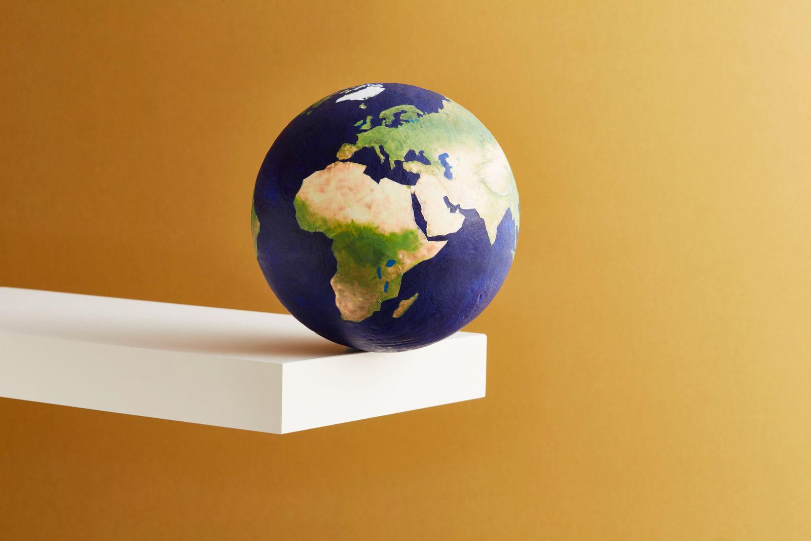 A world globe balanced on the edge of a shelf