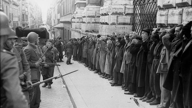 Italian civilians are arrested in Rome by German troops following the partisan attack on occupying soldiers in Via Rasella a day earlier.