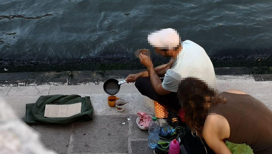 Zwei deutsche Touristen sitzen mit ihrem Gepäck an der Treppe der Rialto-Brücke und kochen sich mit einem kleinen Kaffeekocher einen Kaffee