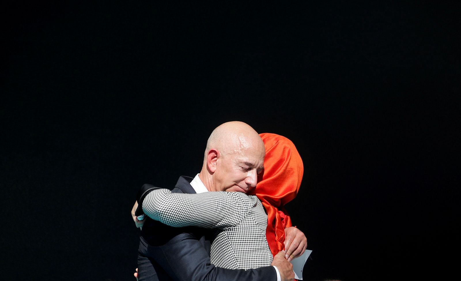 Hatice Cengiz, fiancee of the murdered Saudi journalist Jamal Khashoggi and Jeff Bezos, founder of Amazon and Blue Origin, embrace each other as they attend a ceremony marking the first anniversary of Khashoggi's killing at the Saudi Consulate in Istanbul