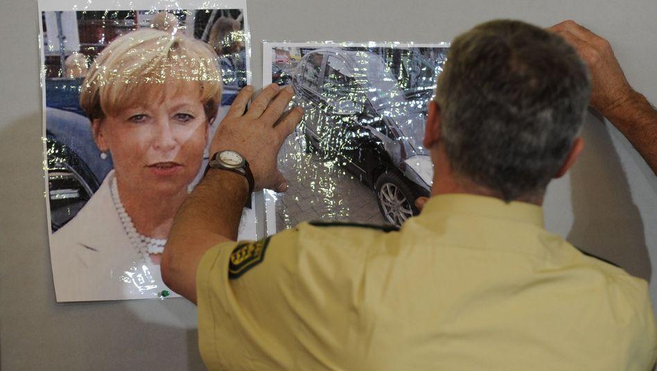 Ein Polizist hängt ein Foto von Bögerl und ihrem Auto auf (Archivbild): 200 Hinweise