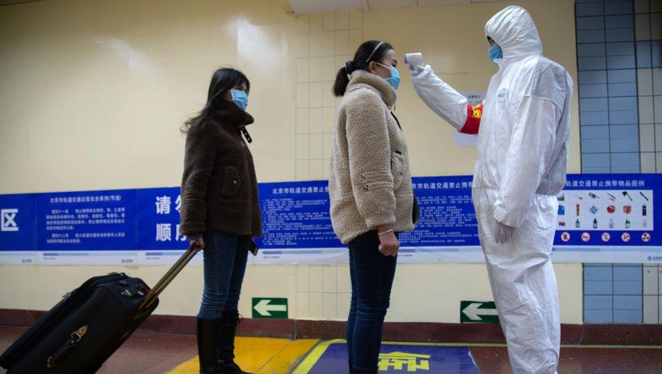 Temperaturkontrolle am U-Bahn-Eingang: Eine Frau in Peking wird von einem Behördenmitarbeiter gescannt
