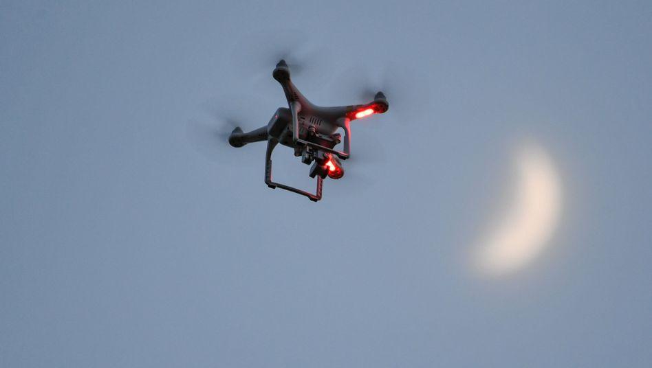 Eine Drohne fliegt kurz vor Sonnenuntergang über eine Wiese, während im Hintergrund der sichelförmige Mond am Himmel zu sehen ist.