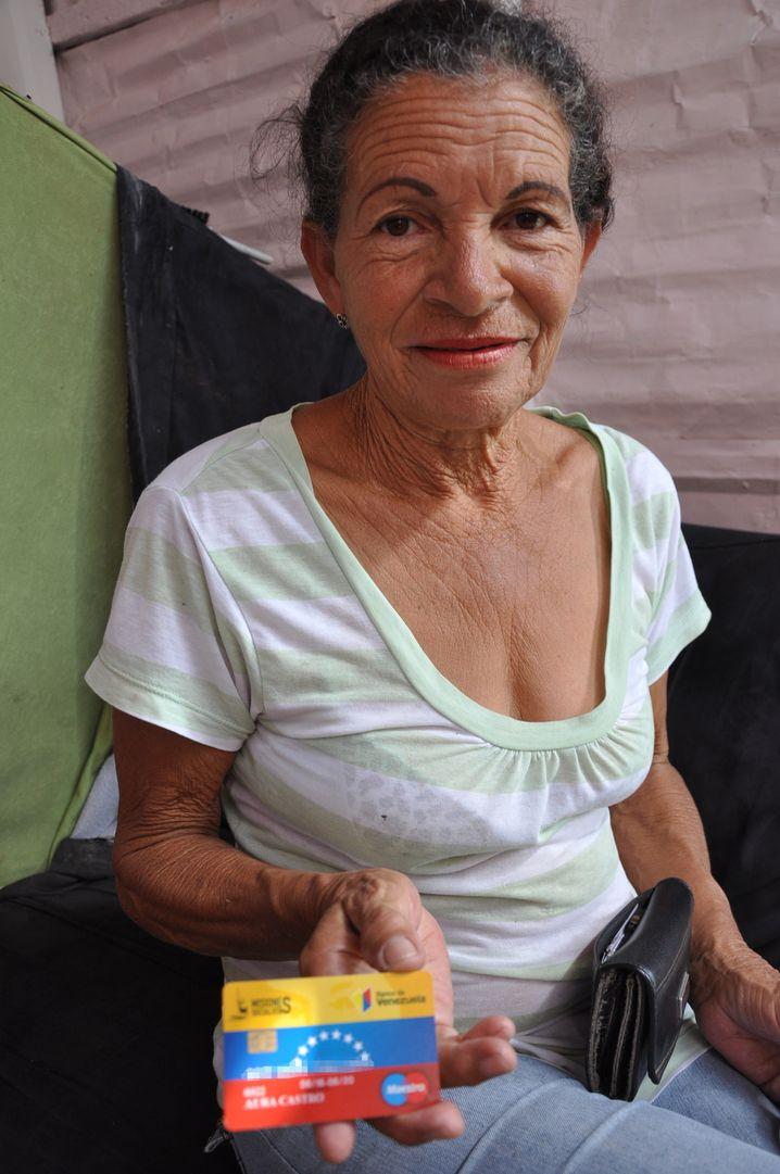 Aura Castro mit Geldkarte der Regierung