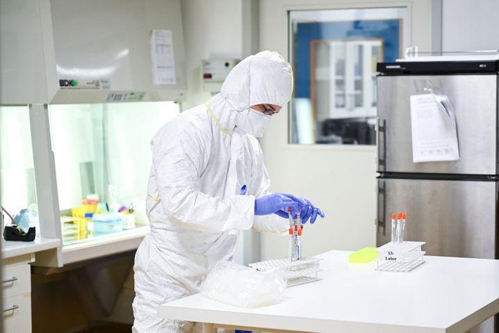 Mitarbeiter in einem Labor bearbeitet Abstrichröhrchen: Die Grippewelle könnte für Engpässe sorgen