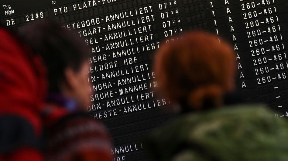 Reisende vor (durchaus ernüchternden) Fluginformationen