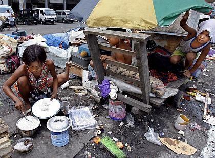 Kleinkinder schauen ihrer Mutter in Manila, Philippinen, beim Kochen zu: Hunger ist für Säuglinge und Kleinkinder besonders bedrohlich