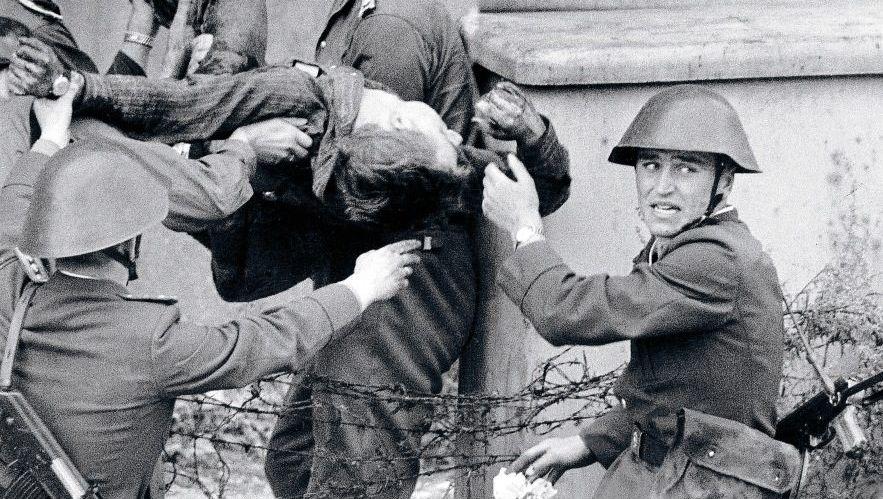 Peter Fechter wird von Grenzsoldaten und Volkspolizisten weggetragen.