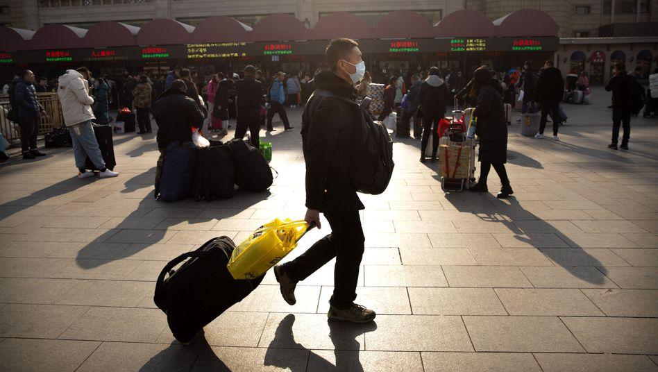 Ein Mann trägt in Peking eine Atemschutzmaske, um sich vor dem Coronavirus zu schützen