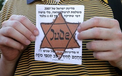 Israeli groups representing Holocaust victims are demanding more money from the German and Israeli governments. Here a protestor holds up a Star of David during an Aug. 5 demonstration in Jerusalem.