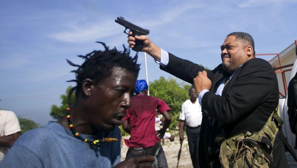 Jean Marie Ralph Féthière feuert seine Waffe vor dem Parlament in Haitis Hauptstadt ab
